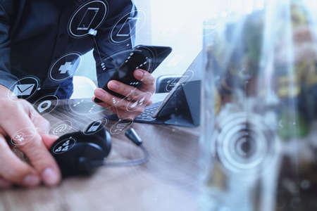 mano del hombre usando auriculares VOIP con teclado de acoplamiento de tableta digital, teléfono inteligente, comunicación conceptual, soporte, centro de atención telefónica y servicio de atención al cliente con florero en primer plano, pantalla de iconos de interfaz virtual Foto de archivo