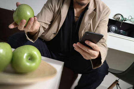 hipster hand using smart phone for mobile payments online business,sitting on sofa in living room,holding green apple in wooden tray
