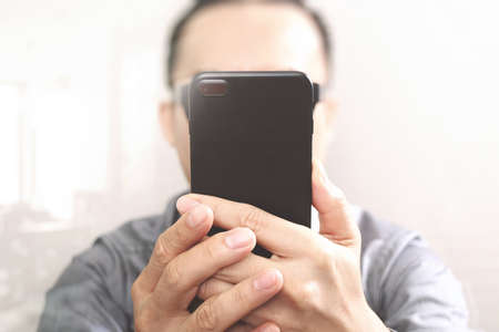 mobile app: Designer hand using mobile payments online shopping,omni channel,customer network connection,wooden desk,icons graphic interface screen,eyeglass Stock Photo