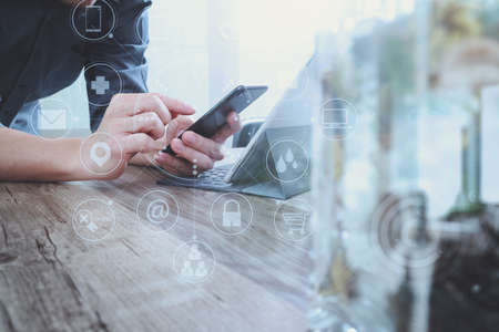 mobile app: businessman hand using smart phone,mobile payments online shopping,omni channel,digital tablet docking keyboard computer,flower glass vase on wooden desk,virtual interface icons screen
