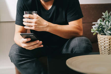 phon: designer man hand with glass of water using smart phon for mobile payments online shopping,omni channel,sitting on sofa in living room,vase rattan with plant and wooden tray on table