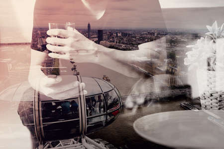 phon: double exposure of designer man hand with glass of water using smart phon for mobile payments online shopping,omni channel,vase rattan with plant and wooden tray on table,London architecture city Stock Photo