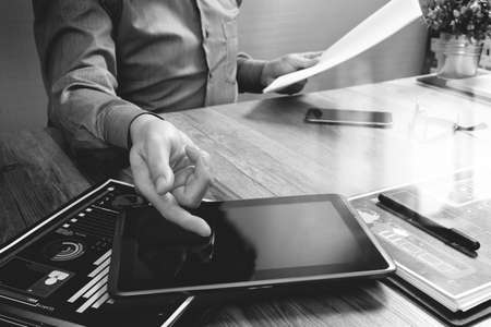 marketing concept: businessman working with digital tablet computer and smart phone and laptop computer with financial business strategy layer effect on wooden desk,black white Stock Photo
