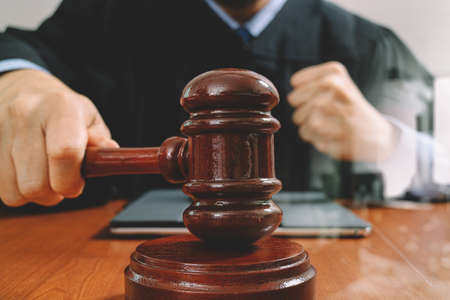 justice and law concept.Male judge in a courtroom with the gavel,working with smart phone,digital tablet computer docking keyboard,eyeglasses,on wood table,filter Stock Photo