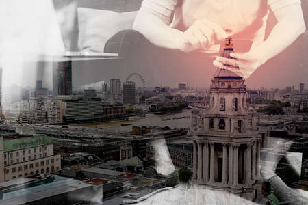 online: double exposure of hipster hand using digital tablet docking keyboard and smart phone for mobile payments online business,omni channel,sitting on sofa in living room,London architecture city