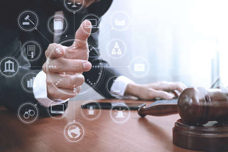 justice and law concept.Male lawyer in office with the gavel,working with smart phone,digital tablet computer docking keyboard,brass scale,on wood table,virtual interface graphic icons diagram Stock Photo