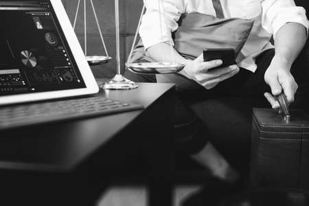 working on computer: Justice and Law context.Male lawyer hand sitting on sofa and working with smart phone,digital tablet computer docking keyboard with gavel and document on living table at home,black and white Stock Photo