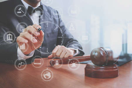 justice and law concept.Male judge in a courtroom with the gavel,working with smart phone,digital tablet computer docking keyboard,brass scale,on wood table,virtual interface graphic icons diagram
