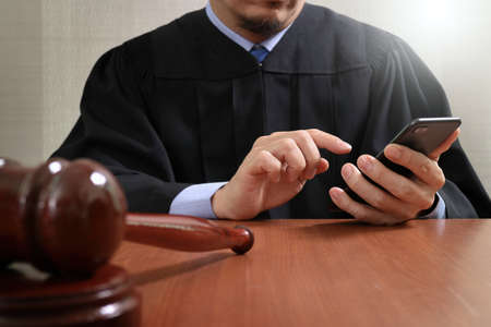 justice and law concept.Male judge in a courtroom with the gavel,working with smart phone computer on wood table Stock Photo