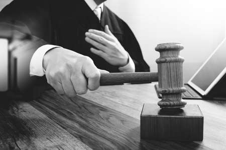 justice and law concept.Male judge in a courtroom striking the gavel,working with digital tablet computer docking keyboard on wood table,black and white