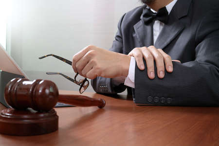 Justice and Law context.Male lawyer hand working with smart phone,digital tablet computer docking keyboard with gavel and document on wood table