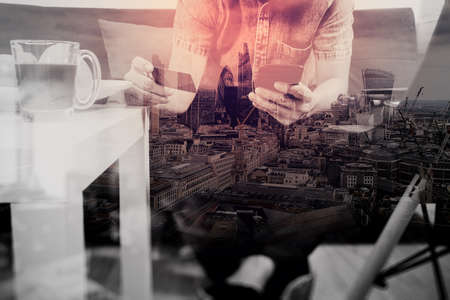 Online Business: double exposure of hipster hand using smart phone,digital tablet docking keyboard,holding credit card payments online business,sitting on sofa in living room,work at home,London architecture city