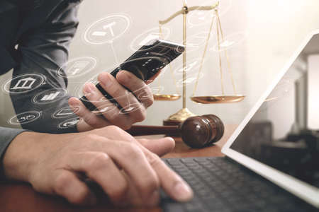 justice and law concept.Male lawyer in office with the gavel,working with smart phone and digital tablet computer and brass scale on wood table,virtual graphic icons screen diagram