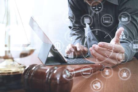 Rechts- en rechtconcept.Male advocaat in kantoor met de hamer, werken met slimme telefoon en digitale tablet computer en messing schaal op houten tafel, virtuele grafische pictogrammen schermdiagram Stockfoto