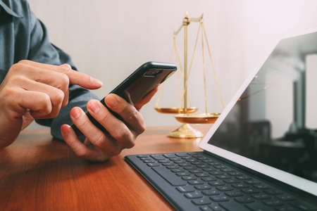 justice and law concept.Male lawyer in office with the balance brass scale,hand working with smart phone and digital tablet computer on wooden desk