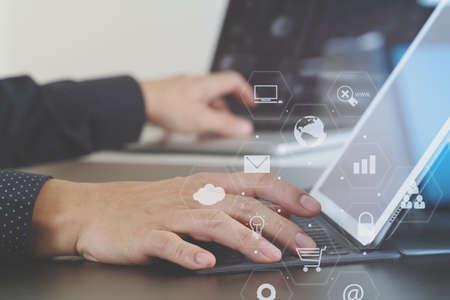 노트북 및 디지털 도킹 작업 사업가 손을 가까이 가상 아이콘 다이어그램과 함께 현대 사무실에서 키보드 태블릿 컴퓨터 스톡 콘텐츠 - 74735121
