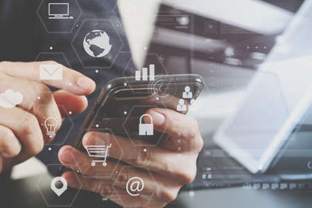 information analysis: close up of businessman hand working with smart phone and laptop and digital tablet computer in modern office with virtual icon diagram Stock Photo