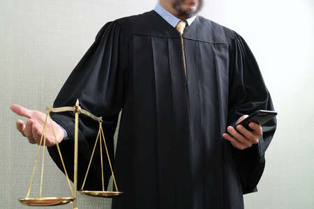 justice and law concept.Male judge in a courtroom with the balance scale and using smart phone Stock Photo
