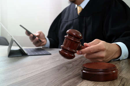 justice and law concept.Male judge in a courtroom with the gavel,working with smart phone, digital tablet computer docking keyboard on wood table