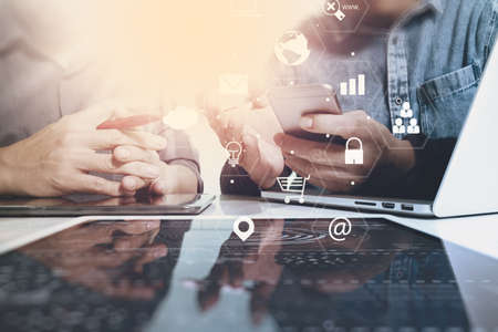 Co-werk team vergadering concept, zakenman met behulp van smartphone en laptop en digitale tablet computer in moderne kantoor met virtuele interface iconen netwerk diagram Stockfoto