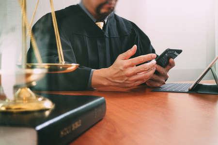 justice and law concept.Male judge in a courtroom with the gavel and working with smart phone and brass scale on wood table
