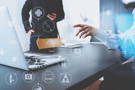 man doctor: Medical co working concept,Doctor working with smart phone and digital tablet and laptop computer to meeting his team in modern office at hospital with virtual diagram