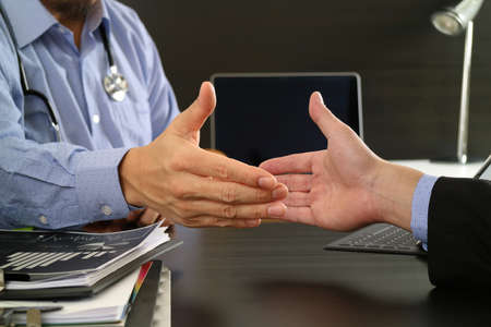 Médico y cuidado de la salud concepto, Médico y paciente agitando las manos en la oficina moderna en el hospital Foto de archivo