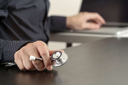 medical doctors: close up of smart medical doctor working with stethoscope and laptop computer on dark wooden desk