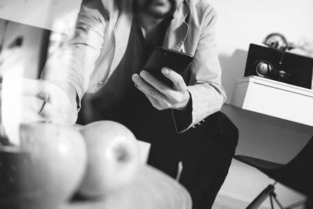 laptop: hipster hand using smart phone for mobile payments online business,sitting on sofa in living room,holding green apples in wooden tray,black and white