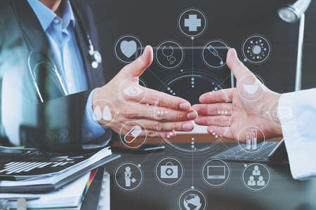 medical doctors: Medical and health care concept,Doctor and patient shaking hands in modern office at hospital with virtual computer interface graphic and icons diagram