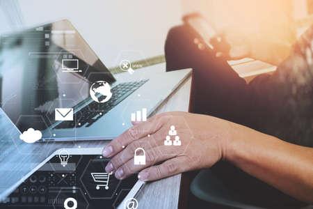 Homme d'affaires travaillant avec ordinateur portable et tablette numérique et livre et document sur bureau en bois dans un bureau moderne avec interface d'icônes virtuelles