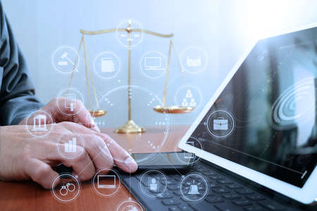 justice and law concept.Male lawyer in office with the balance brass scale,hand working with smart phone and digital tablet computer on wooden desk,virtual graphic icons screen diagram