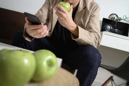 popular: hipster hand using smart phone for mobile payments online business,sitting on sofa in living room,holding green apple in wooden tray