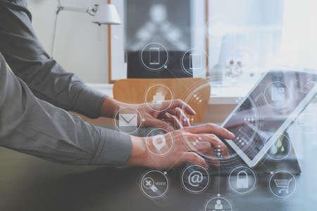 Uomo d'affari o progettista che utilizza il computer digitale della compressa sullo scrittorio nero in ufficio moderno con lo schema della rete delle icone grafiche dell'interfaccia virtuale Archivio Fotografico - 74831300