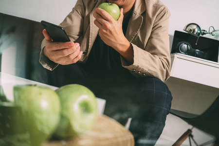 mobile phone screen: hipster hand using smart phone for mobile payments online business,sitting on sofa in living room,holding green apple in wooden tray,filter