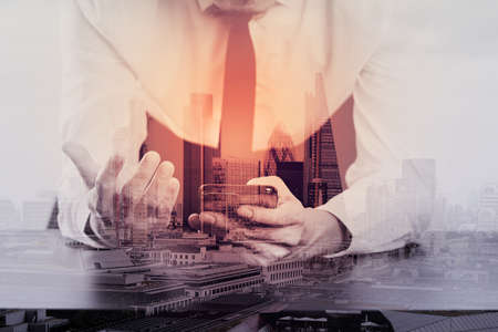 office desk: close up of businessman working with smart phone on wooden desk in modern office with London city exposure