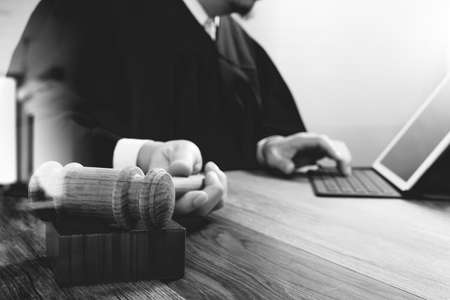 book: justice and law concept.Male judge in a courtroom with the gavel,working with smart phone,digital tablet computer docking keyboard on wood table,black and white