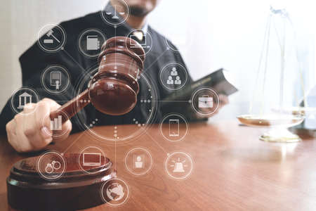 justice and law concept.Male judge in a courtroom with the gavel and working with book and brass scale on wood table with virtual interface graphic icons diagram