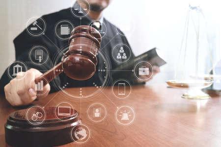 justitie en recht concept. Mannelijke rechter in een rechtszaal met de hamer en werken met boek en koperen schaal op houten tafel met virtuele interface grafische pictogrammen diagram