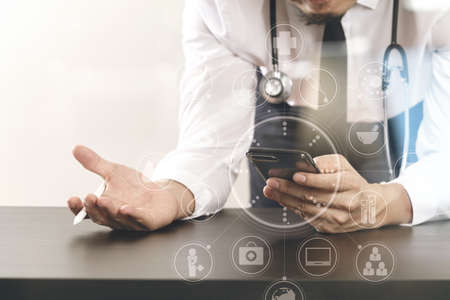 medical doctors: close up of smart medical doctor working with smart phone and stethoscope on dark wooden desk with virtual icon diagram