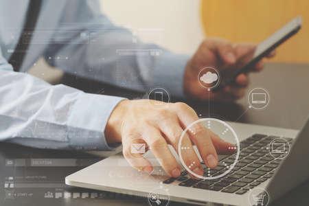 Sluit omhoog van zakenman het werken met mobiele telefoon en laptop computer op houten bureau in modern bureau met het virtuele diagram van het werkelijkheidspictogram