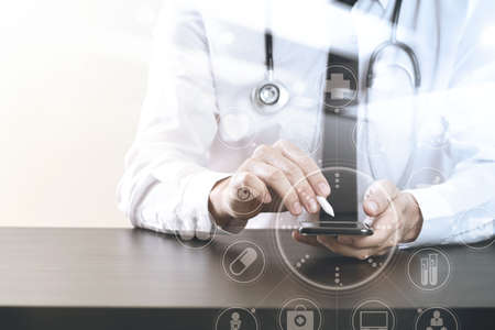 mobile: close up of smart medical doctor working with smart phone and stethoscope on dark wooden desk with virtual icon diagram