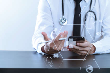 close up of smart medical doctor working with smart phone and stethoscope on dark wooden desk with virtual icon diagram Stock Photo - 76802827