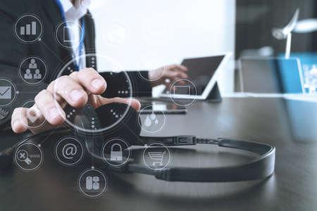 Uomo che utilizza cuffia VOIP con tablet digitale e computer portatile come comunicazione concettuale, supporto, call center e assistenza clienti con diagramma a icona virtuale