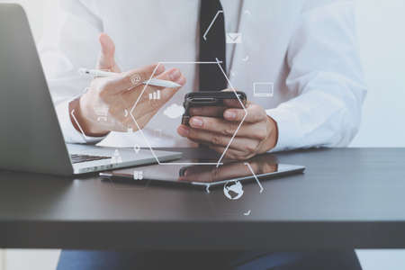 project: close up of businessman working with mobile phone on wooden desk in modern office with virtual icon diagram Stock Photo