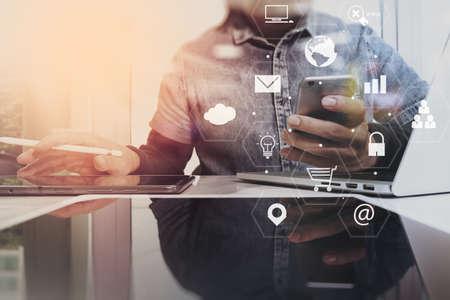스마트 전화 및 노트북 컴퓨터 가상 책상 인터페이스를 사용 하여 현대 사무실에서 나무 책상에서 작동하는 사업가