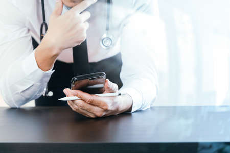 close up of smart medical doctor working with smart phone and stethoscope on dark wooden desk with glass reflected view