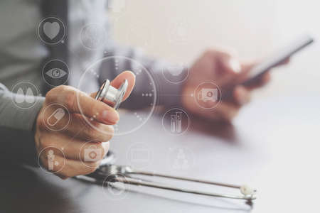 screen: close up of smart medical doctor working with stethoscope and mobile phone on dark wooden desk in modern hospital with virtual reality icon diagram