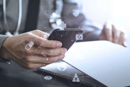携帯電話およびラップトップ コンピューターと聴診器の使用バーチャルリアリティ アイコン ダイアグラム暗い木製机の上スマート医師のクローズ  写真素材