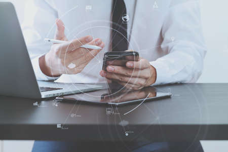Hands of businessman using mobile phone in modern office with laptop and digital tablet computer with VR icon diagram 스톡 콘텐츠 - 94486135